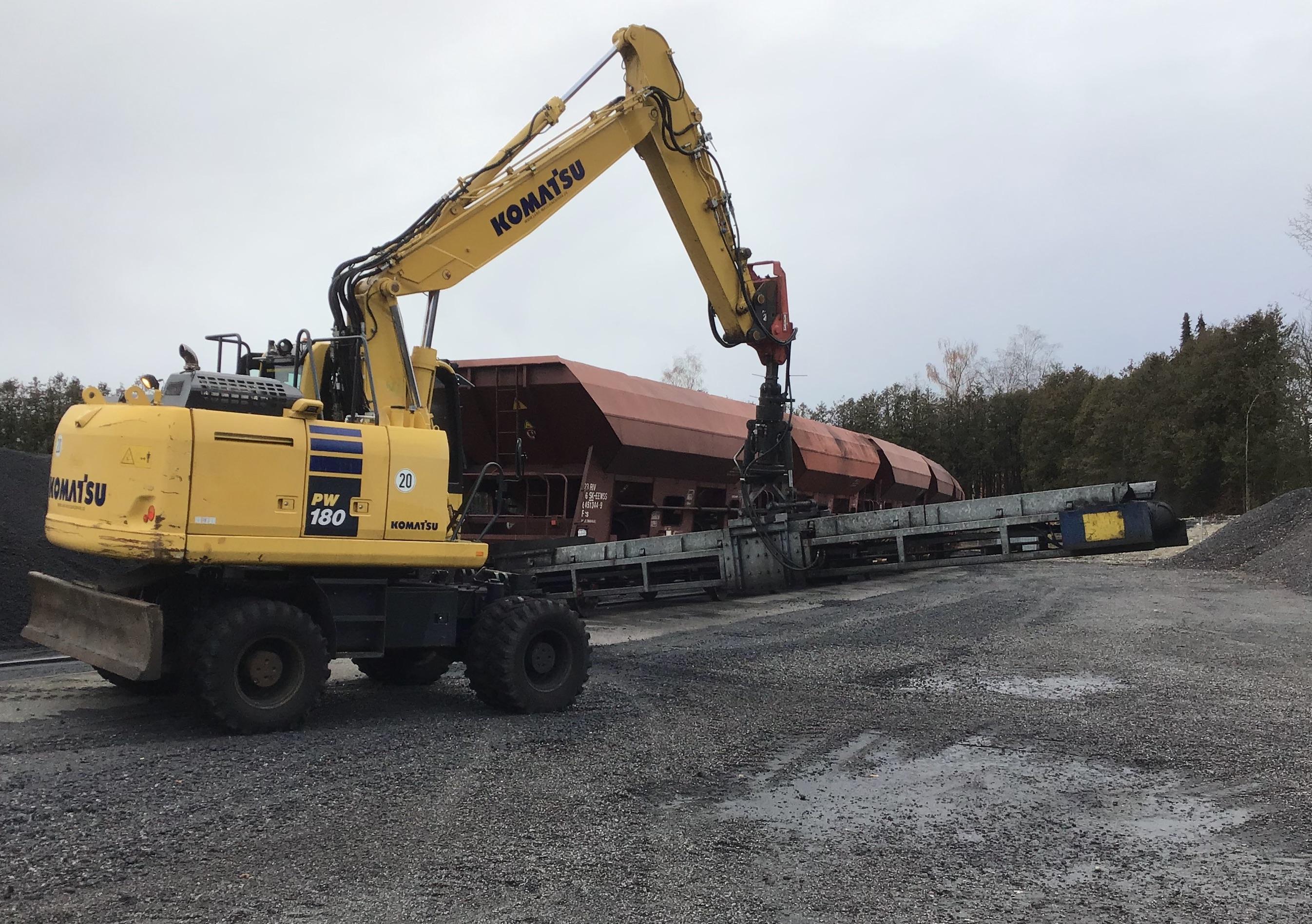 Mit dem Mobilbagger PW180 und dem Förderband wird der Schwarzstoff vom Güterwagen entladen und in das Freilager transportiert